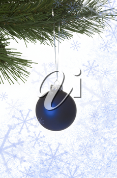 Image of blue decorative toy ball hanging on spruce branch surrounded by snowflakes