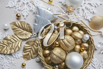 Golden nuts, shell, beads and white ball lying in the basket on the christmas backdrop