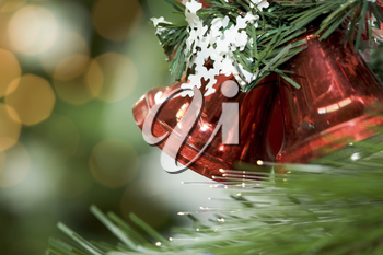 Close-up of red toy bells hanging on green spruce branch decorated with paper snowflake