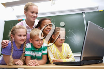 Portrait of pupils looking at the laptop with teacher near by