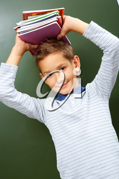 Portrait of smart lad with copybooks on head looking at camera