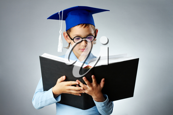 Portrait of cute lad in eyeglasses and student hat reading book
