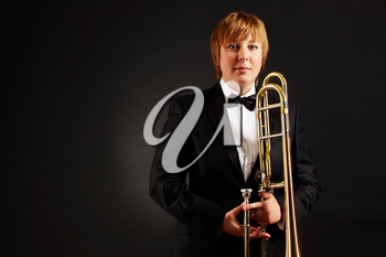 Portrait of young female with trombone looking at camera on black background