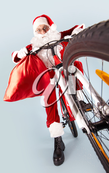 Photo of amazed Santa Claus with red sack on bike