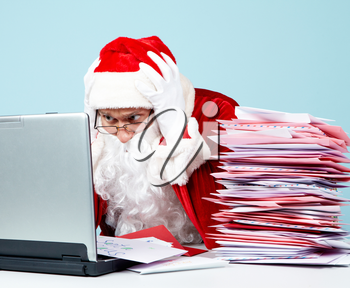 Portrait of terrified Santa Claus touching head in front of laptop