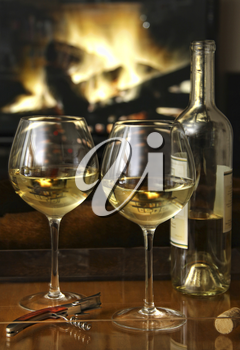 Royalty Free Photo of a Bottle and Two Glasses of Wine in Front of a Fire