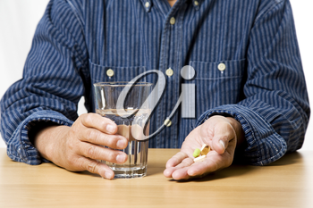 A shot of a senior man taking medicine with a glass of water