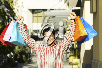 A happy young man carrying shopping bags at an outdoor mall