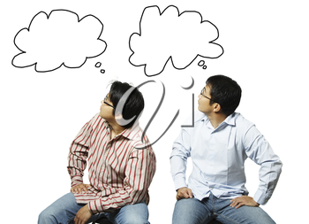 A conceptual shot of two businessmen looking at their own thoughts