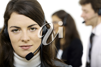 Customer service team working in headsets, smiling. Woman in front.