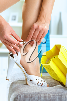 Closeup photo of female leg and hands. Woman fitting her high heel shoe.