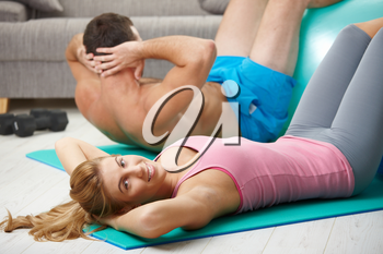 Young couple doing abdominal crunch using fit ball at home.