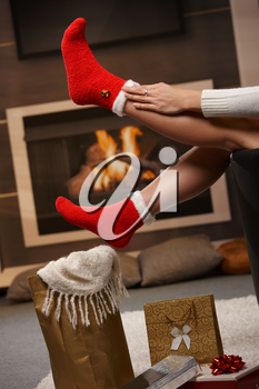 December: female legs in santa claus socks at christmas in front of fireplace. Gifts on the floor.