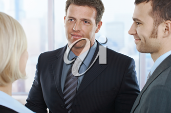 Businessmen looking at businesswoman standing in office, smiling.
