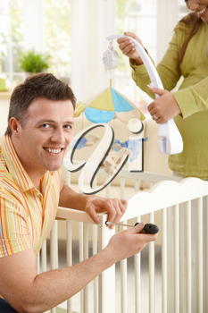 Portrait of man fixing baby bed, smiling at camera, smiling expectant woman holding baby toys in background.
