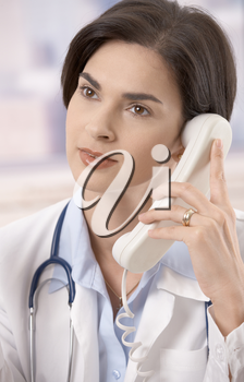 Attractive mid-adult caucasian female doctor talking on landline phone, looking away.