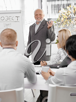 Senior businessman doing presentation to team, gesturing and smiling, standing at whiteboard.