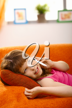 Schoolgirl lying on couch talking on mobile phone, smiling,