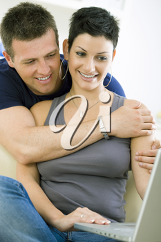 Happy young couple browsing internet on laptop computer at home, smiling.