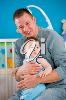 Portrait of baby boy ( 1 year old ) and father at children's room, smiling.