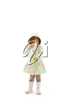 Small girl wearing raincoat and boots, smelling pink flower. Isolated on white background.