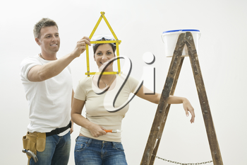 Happy young couple playing with ruler while planning their new home.  Isolated on white background.