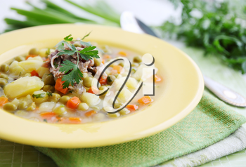 Hot soup with fresh green peas and herbs