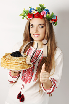Ukrainian woman holds a plate of pancakes and caviar showing ok gesture