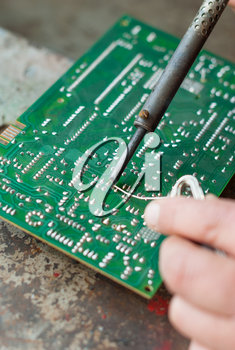 Man with soldering iron to solder electronic board.