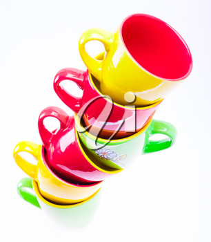 Beautiful yellow, red, green color cups. Leaning tower stack of clean different cups isolated on white background
