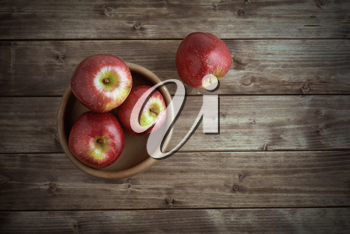 Red ripe apples in a saucer on the old wooden table