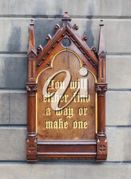 Decorative wooden sign hanging on a concrete wall - You will either find a way or make one