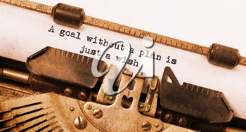 Vintage typewriter, old rusty, warm yellow filter, a goal without a plan is just a wish