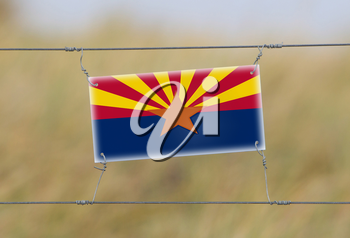 Border fence - Old plastic sign with a flag - Arizona