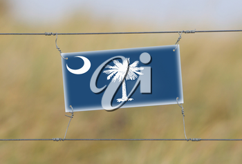 Border fence - Old plastic sign with a flag - South Carolina