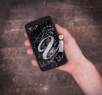 Hand holding a mobile phone with a broken screen, black display
