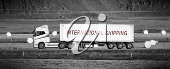 White trruck driving through a rural area - International shipping