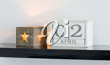 White block calendar present date 3 and month April on white wall background