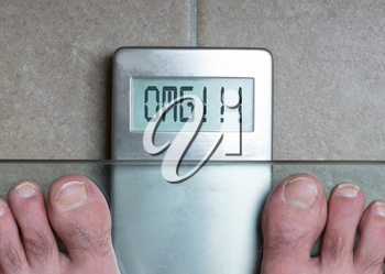 Closeup of man's feet on weight scale - OMG