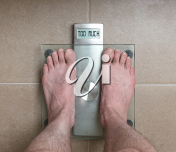 Closeup of man's feet on weight scale - Too much