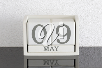 White block calendar present date 9 and month May on white wall background