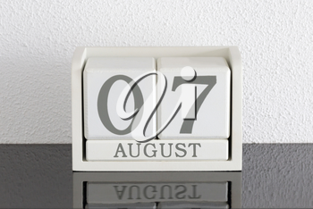 White block calendar present date 7 and month August on white wall background