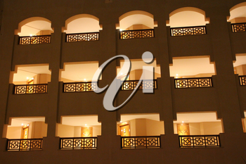 Modern resort building with illuminated windows and balconies in evening. Place for relax in resort