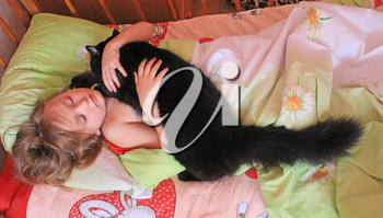 Little girl laying in bed together with her cat. Together with your pet. Black cat laying on its little mistress. Domestic pet. Intimate friendship. Cat loves its little mistress