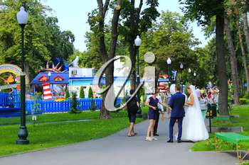 married couple with friends walk in central Horkyi park with big trees in Kharkiv. 07 August 2016 in Kharkiv.