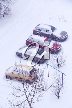 Parked cars covered with snow. Bad weather in town. Snowy day. Blizzard in city. Automobiles trapped in snow. Excessive precipitation in winter city. Urban scene. Weather concept
