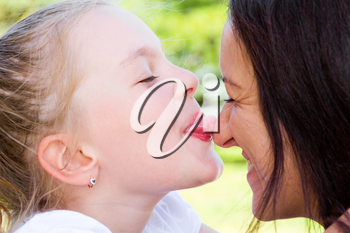 Photo of kissing mother and daughter in summer