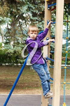 Cute boy climbing a rope ladder on the playground