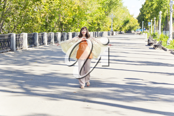 Pregnant woman with brown hair walking on embankment widely spaced arms