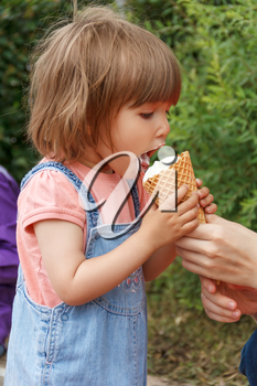 Vertical photo of cute girl are eating icecream in summer time
